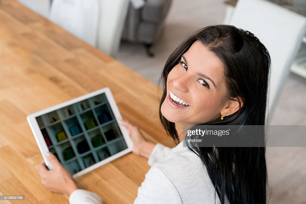 Happy woman shopping online on a tablet computer : Stock Photo