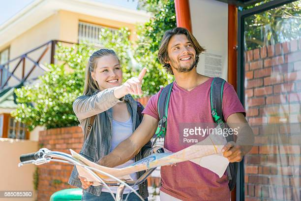 Happy woman showing direction while man holding map in city