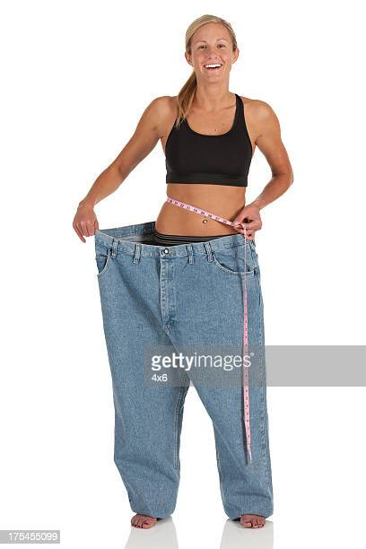 Happy woman showing her loosing weight