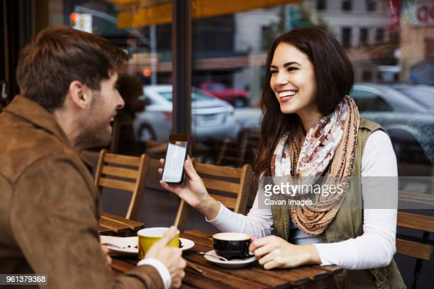 Happy woman showing mobile phone to boyfriend while enjoying coffee at cafe
