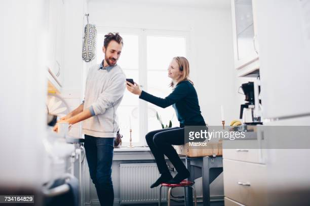 Happy woman showing mobile phone to man in kitchen at home