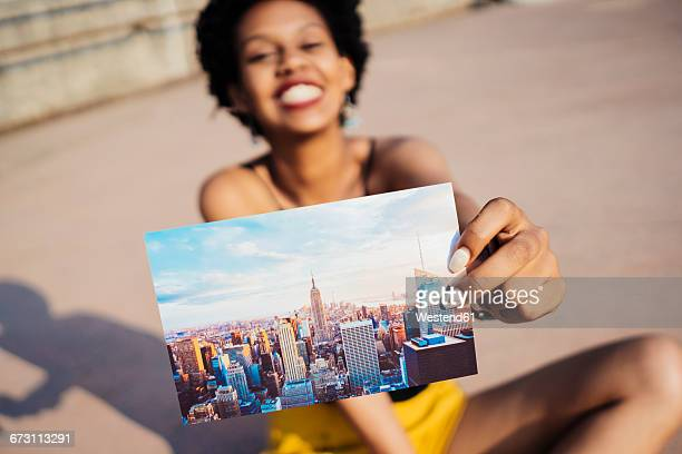 Happy woman showing postcard of New York City