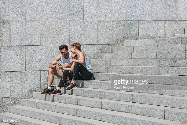Happy woman showing smart phone to friend while sitting on steps by wall