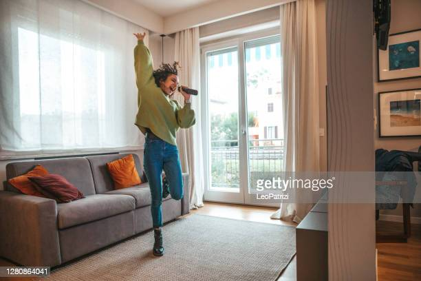 happy woman singing in the living room - dancer stock pictures, royalty-free photos & images