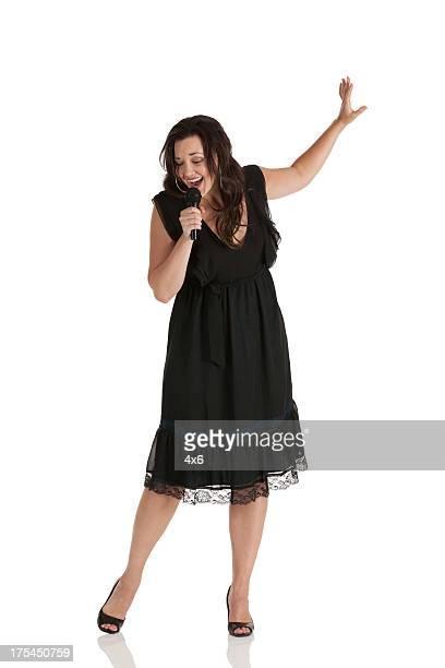 happy woman singing into a microphone - zanger stockfoto's en -beelden