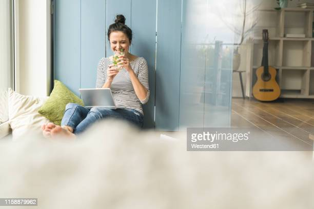 happy woman sitting at the window at home working with laptop and drinking infused water - infused water stock pictures, royalty-free photos & images