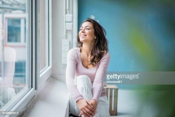 happy woman sitting beside window sill looking out of window - bien être photos et images de collection