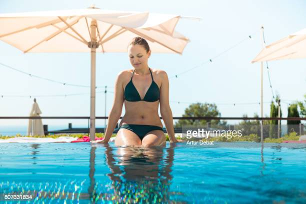 Happy woman sitting in outdoor overflowing swimming pool during weekend days of relax and spa in a luxury place during travel vacations.
