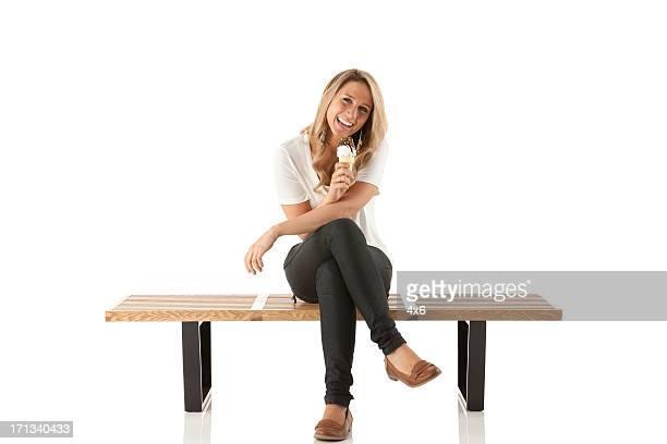 Felice donna seduta su una panchina e gelato