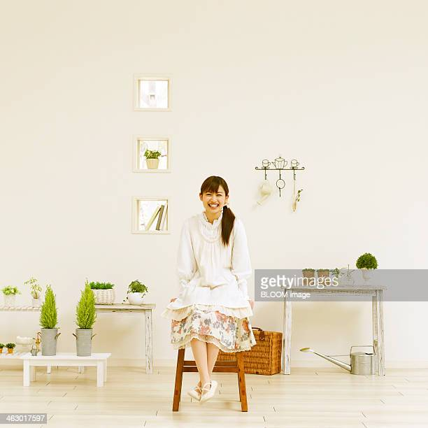 happy woman sitting on a chair - tidy room stock pictures, royalty-free photos & images