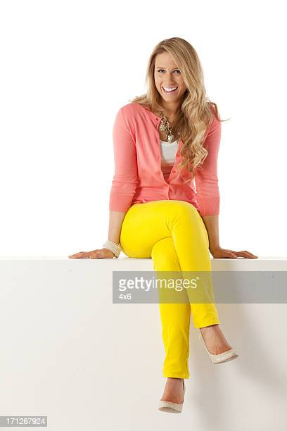 happy woman sitting on a ledge - sitting stock pictures, royalty-free photos & images