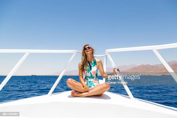 happy woman sitting on boat against clear sky - badkleding stockfoto's en -beelden