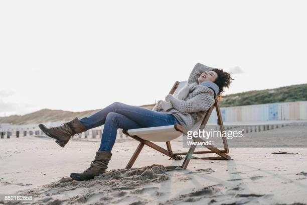 Happy woman sitting on deckchair on the beach