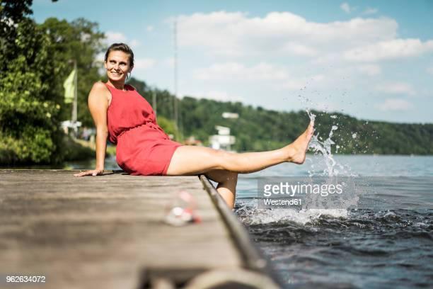 happy woman sitting on jetty at a lake - エッセン ストックフォトと画像
