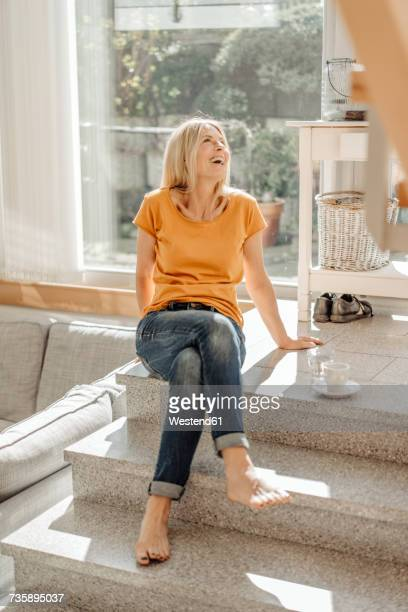 happy woman sitting on stairs at home - donne bionde scalze foto e immagini stock