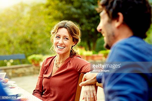 happy woman sitting with man at outdoor table - 40 49 jaar stockfoto's en -beelden