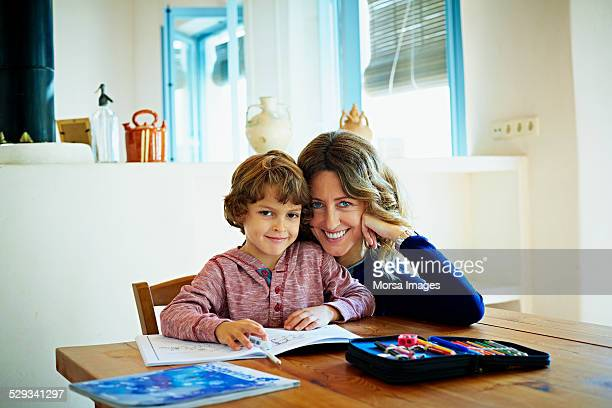 Happy woman sitting with son studying at home