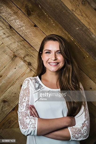 Happy woman standing against wooden wall