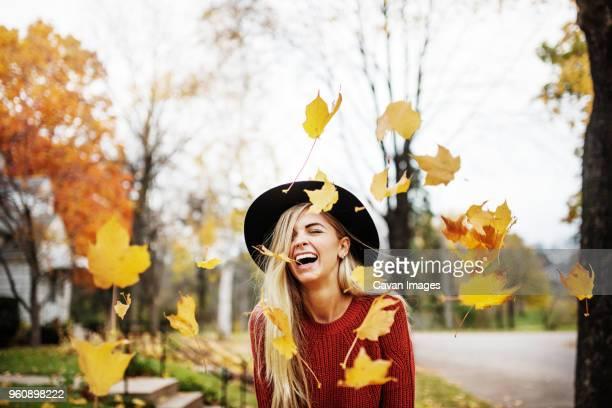 happy woman standing amidst flying autumn leaves - blatt pflanzenbestandteile stock-fotos und bilder