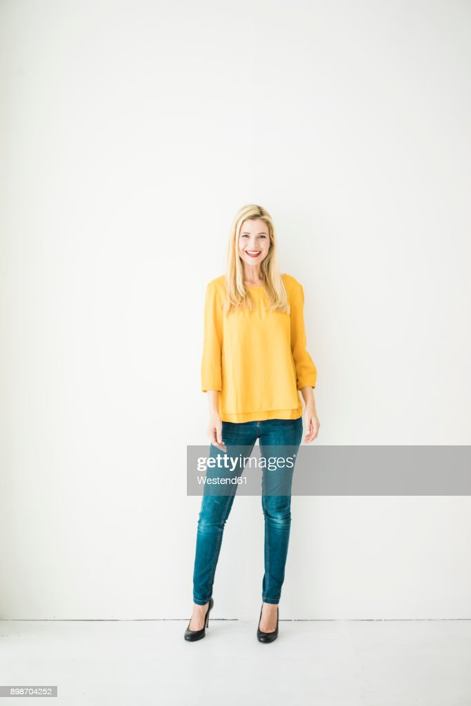 Happy woman standing at a wall : Foto de stock