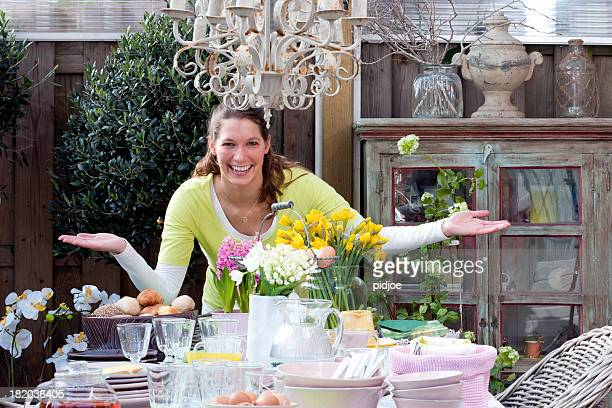happy woman standing at Easter breakfast picnic table