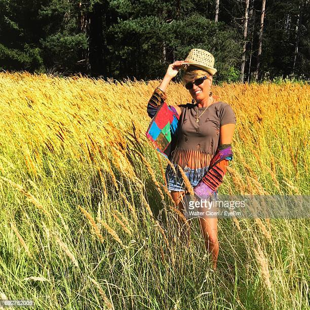 happy woman standing by crops growing on field - walter ciceri foto e immagini stock