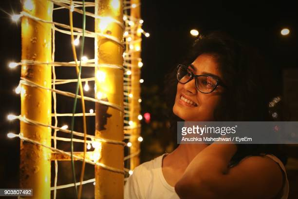 Happy Woman Standing By Illuminated String Lights At Night