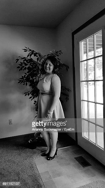 Happy Woman Standing By Potted Plant And Window At Home