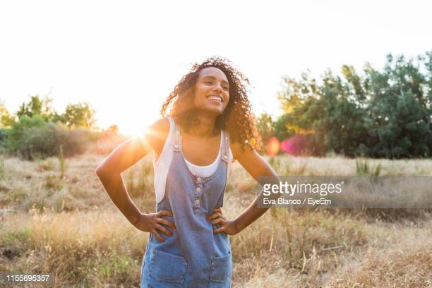 happy woman standing on field during sunny day - hand on hip stock pictures, royalty-free photos & images