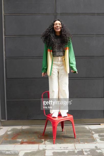 happy woman standing on red chair - farbquadrat stock-fotos und bilder