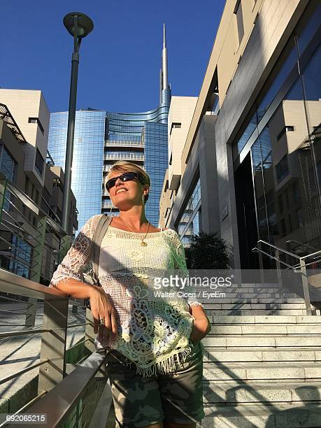 happy woman standing on steps against modern buildings in city - walter ciceri foto e immagini stock
