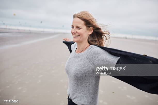 happy woman standing on the beach - mid adult women stock pictures, royalty-free photos & images