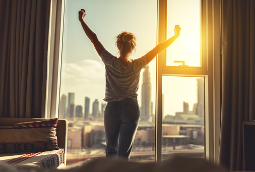 happy woman stretches and  opens curtains at window in morning 912257262