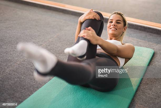 Happy woman stretching during a training class in a gym.