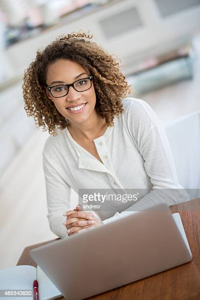 Happy woman student using a laptop