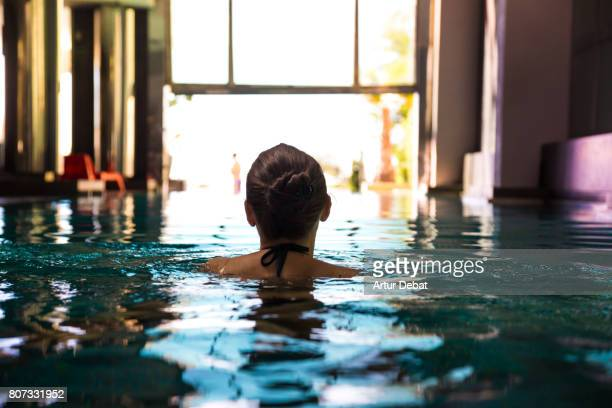Happy woman swimming in indoor swimming pool during weekend days of relax and spa in a luxury place during travel vacations.