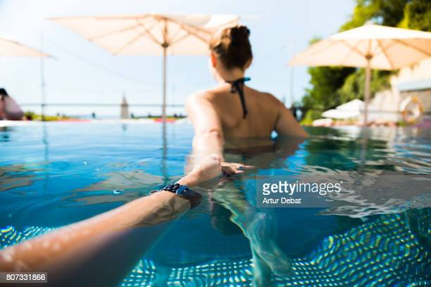happy woman swimming in outdoor overflowing swimming pool during romantic weekend days of relax and spa in a luxury place during travel vacations with boyfriend holding hands from boyfriend personal perspective. follow me. - zuid europese etniciteit stockfoto's en -beelden