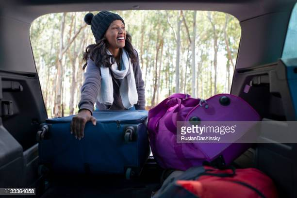 happy woman taking a road trip break, taking out a bag from the car trunk. - black boot stock pictures, royalty-free photos & images