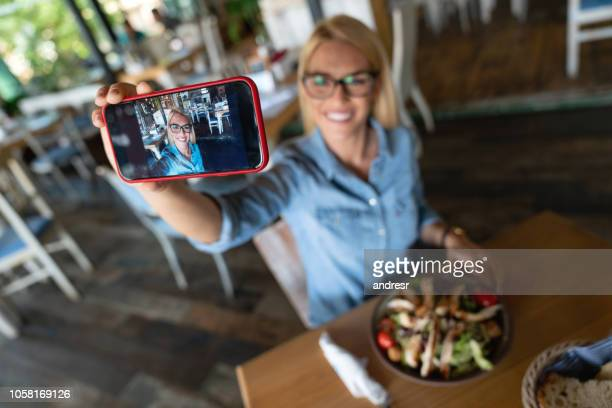 happy woman taking a selfie at a restaurant - self portrait stock pictures, royalty-free photos & images