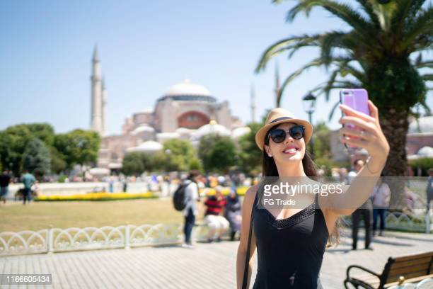 happy woman taking a selfie in front of aya sofya, istambul, turkey - hagia sophia istanbul stock pictures, royalty-free photos & images