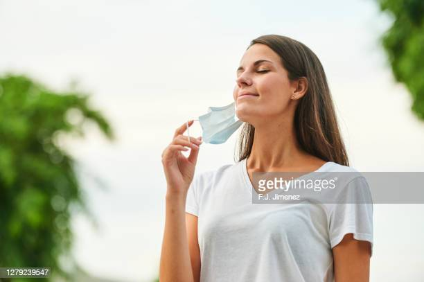 happy woman taking off mask to breathe - absence stock pictures, royalty-free photos & images