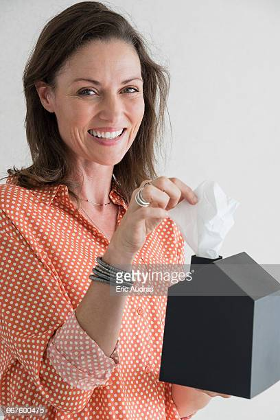 Happy woman taking out tissue paper from a box