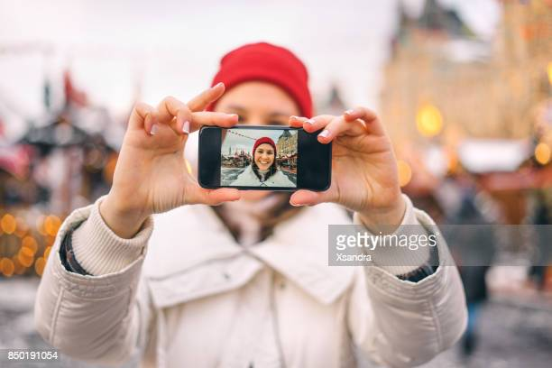 happy woman taking photos an the christmas market - influencer stock pictures, royalty-free photos & images