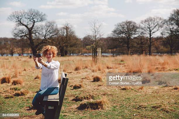 Happy Woman Taking Selfie While Sitting On Bench At Field