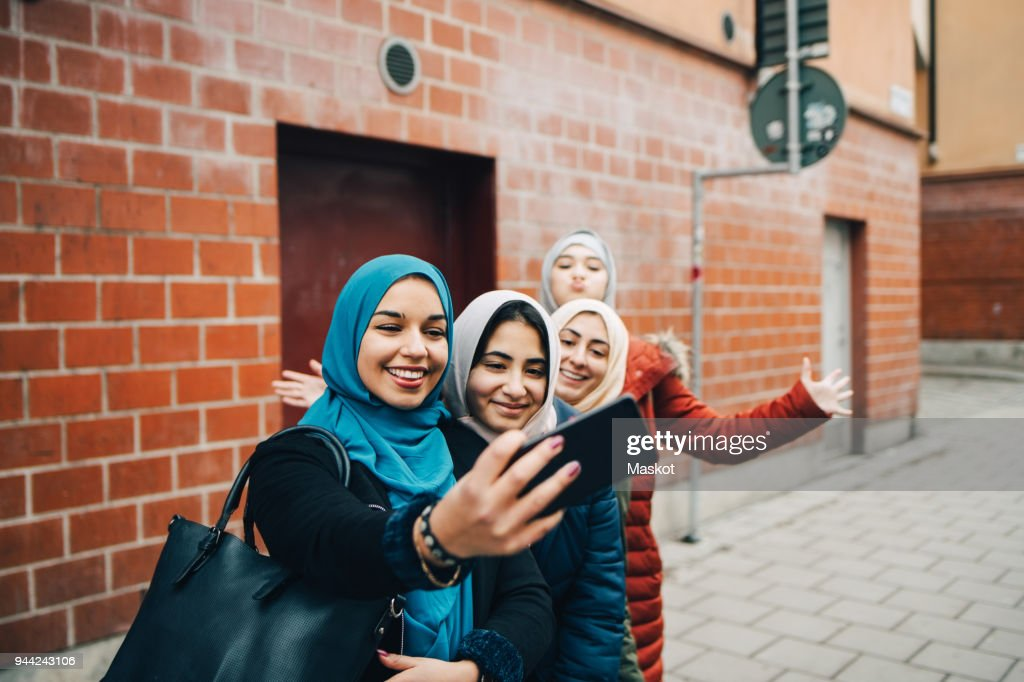 Happy woman taking selfie with female friends on sidewalk against building in city : Stock Photo