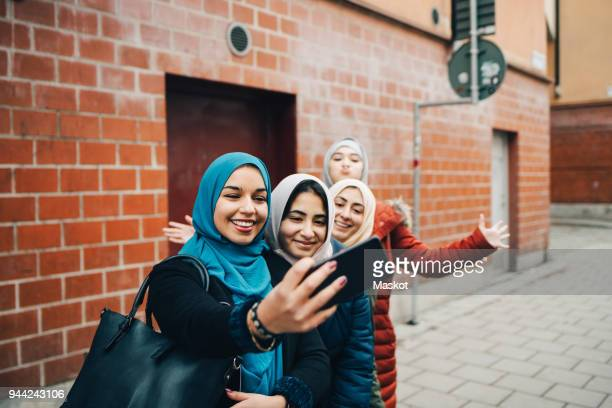 Happy woman taking selfie with female friends on sidewalk against building in city