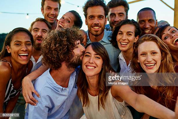 Happy woman taking selfie with friends