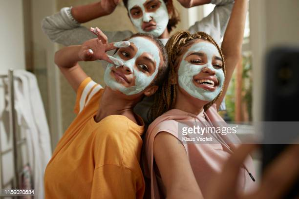 happy woman taking selfie with friends wearing cream - skin care stock pictures, royalty-free photos & images