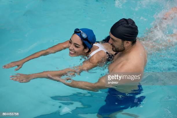 Glückliche Frau Schwimmunterricht mit einem Lehrer zu nehmen