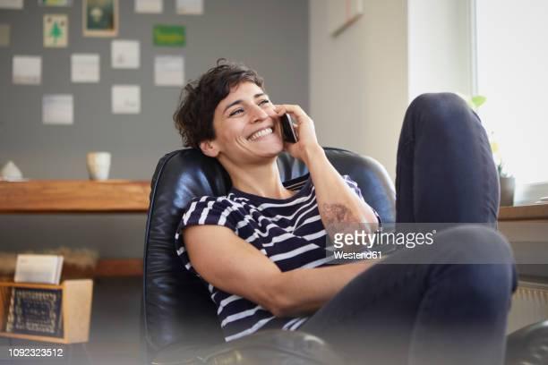 happy woman talking on cell phone at home - frauen über 30 stock-fotos und bilder